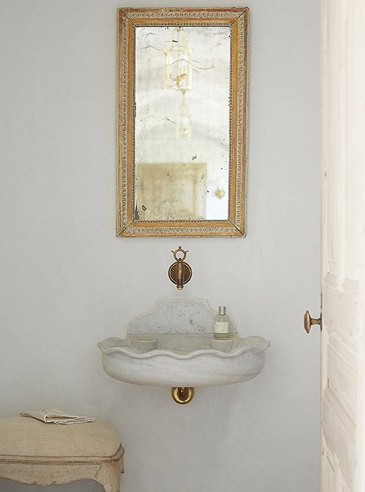 The powder room reflects the couple's signature mix of rustic and refined. A marble sink found in Belgium is suspended on the wall, and a fountain spout finds new life as a faucet. The mirror is from Marston Luce Antiques in Washington, DC.