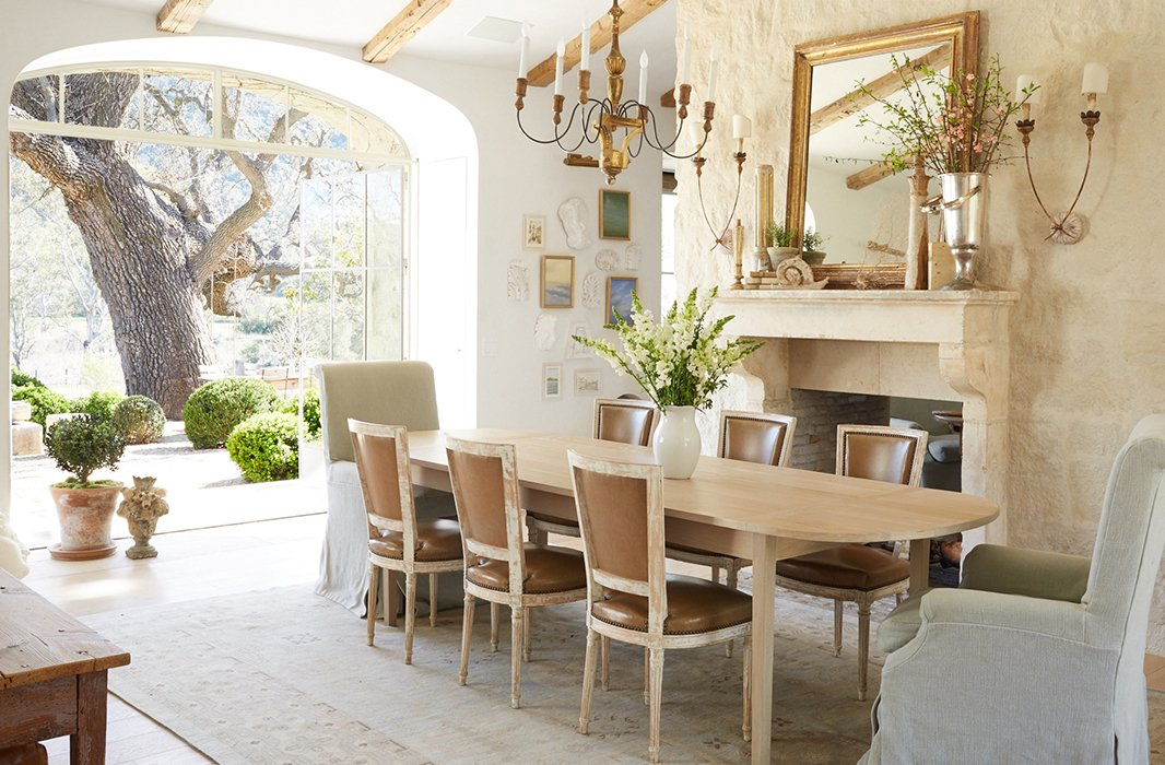 "Knowing that they wouldn't use a formal dining room, the couple created a flexible space. ""We use it for meetings, school projects, and of course family meals,"" says Brooke. Antique side chairs are paired with Giannetti Home armchairs."