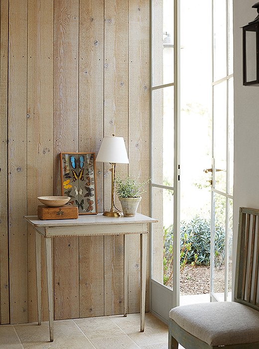A wall of weather-grayed cedar in Brooke's office is a backdrop for an antique Swedish table and a framed set of pressed butterflies. The limestone floor from the covered porch just outside runs through the entire room.
