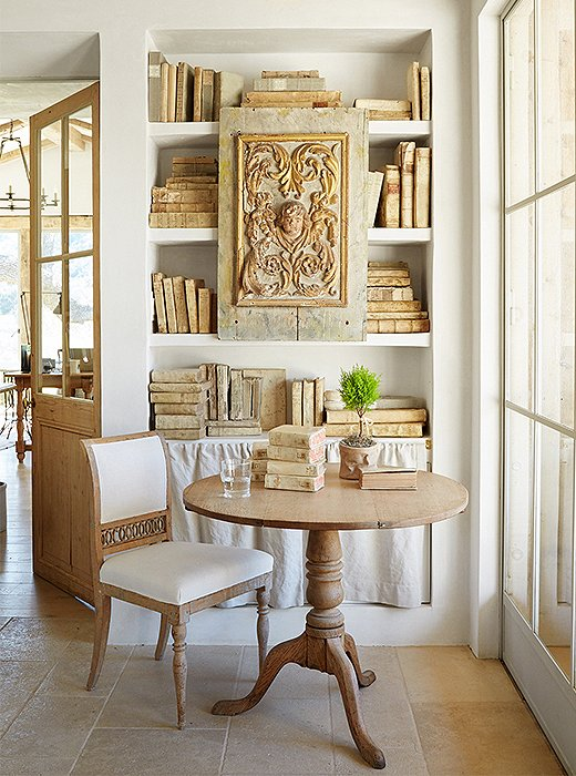The exposed plaster shelves in Brooke's office display her collection of antique paper and vellum books. Brooke meets with her design associates at the table, while just beside it a natural linen curtain hides dog and rabbit supplies.