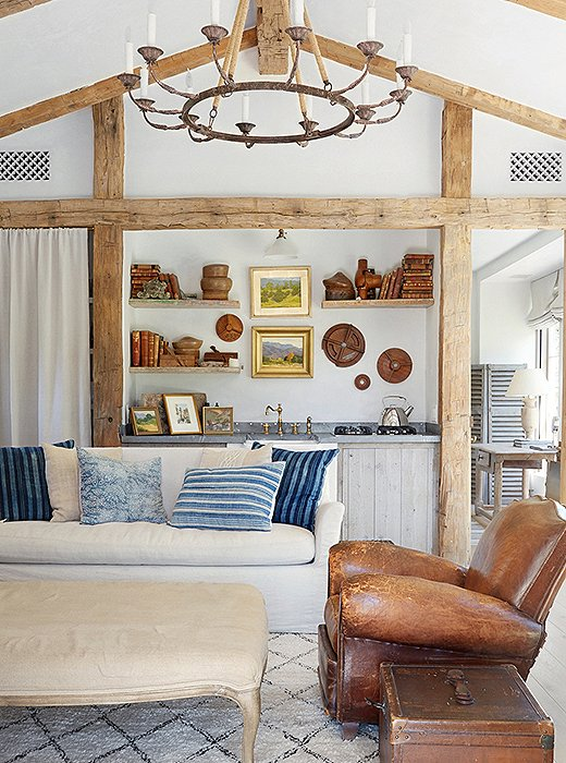 "The guesthouse feels like an ""artist's studio""—a bucolic design filled with collections of classical pieces including vintage landscape paintings and ornamental plaster. Antique barn beams frame the kitchen area."