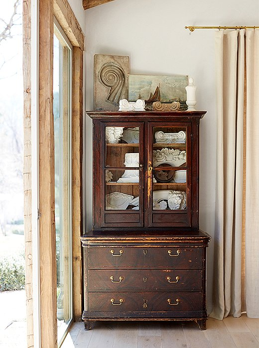"An antique Italian cabinet with embossed leather interior adds storage and is a display place for ornamental plaster pieces. ""Like in Steve's office, we used large single-pane glass to provide great views of the pond and the donkeys,"" says Brooke."