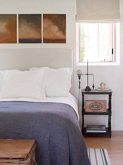 """Steve's paintings were the inspiration for the palette of the guest bedroom,"" says Brooke. A linen headboard, a woven blanket, and a striped rug add texture. The vintage industrial light with its original cloth-covered wiring is a unique bedside lamp."