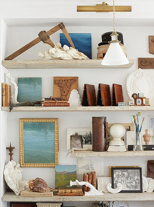 Art leaned on shelves in multiples creates a charmingly laid-back vignette. Photo by David Tsay.
