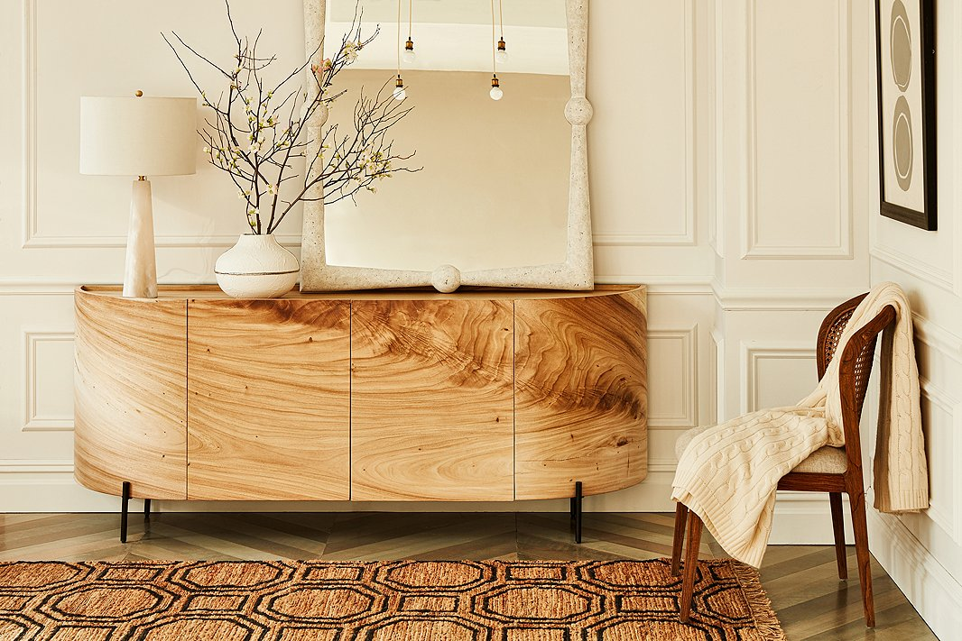 Shown above: the Bryn sideboard, which has shelves behind its doors; the Scarlett wall mirror; and the Hexile jute rug.