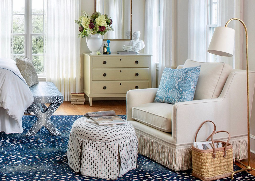The cozy charm of the Liza Skirted Ottoman in Midnight and the Portsmouth Chair in Cream Linen prevents the animal prints of the bench and the rug from making the room feel too glam.