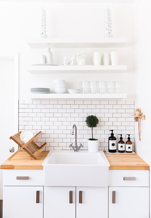 All-white accessories on the kitchen shelves make for a look that's not just clean but chic as well.