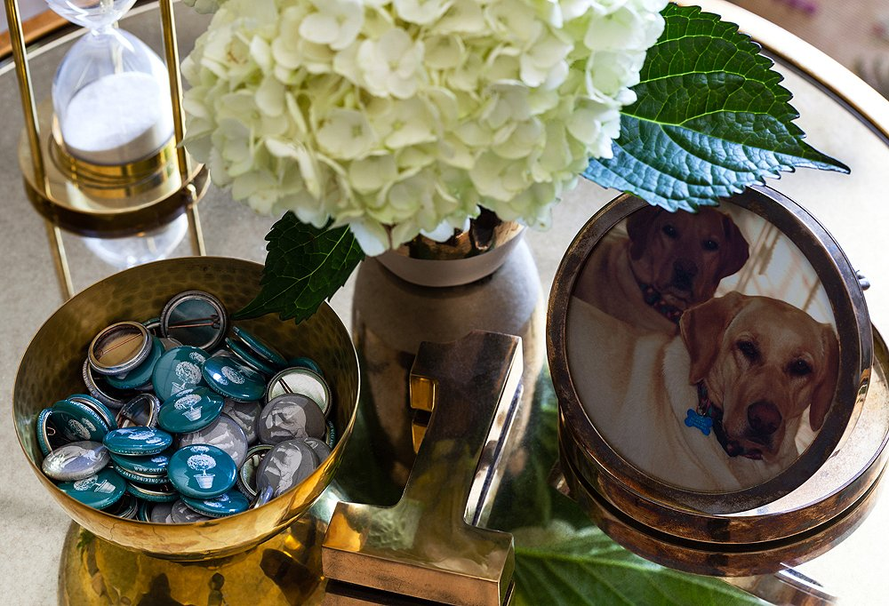 A bowl of buttons from a recent One Kings Lane party sits next to a framed picture of Susan's two dogs, Maggie and Chloe. Hydrangeas are Susan's office flower of choice.
