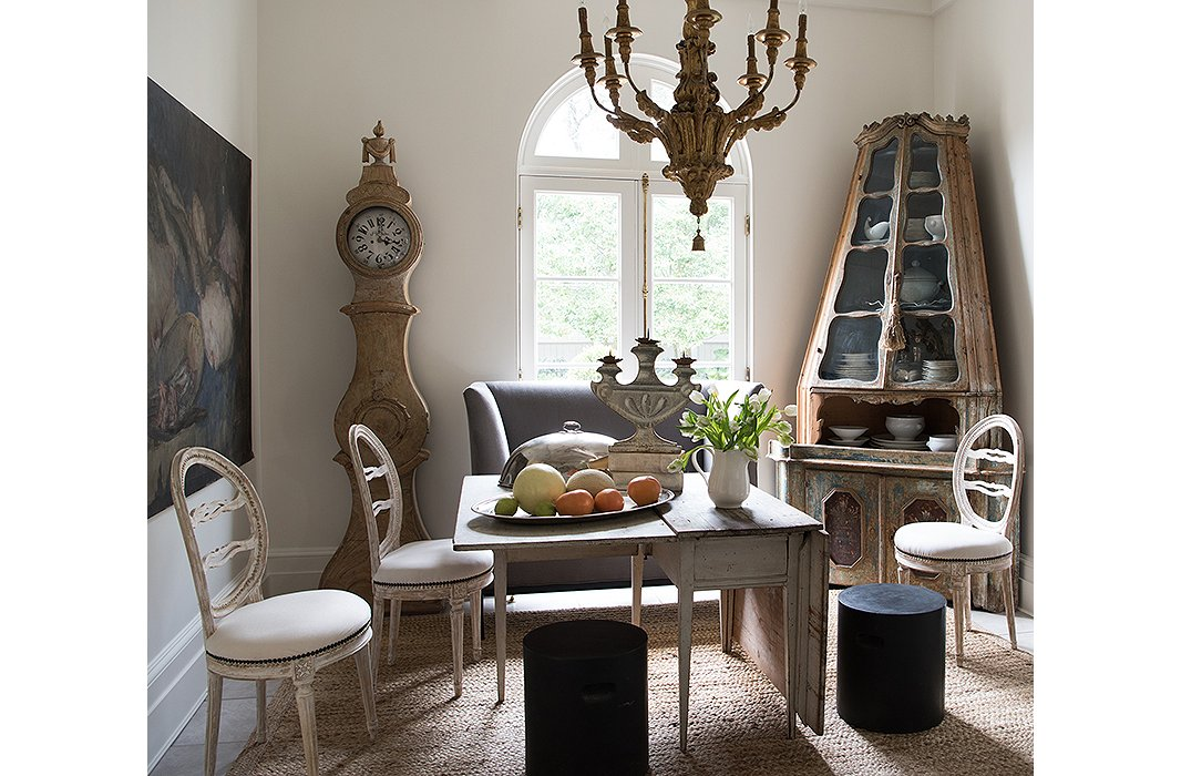 An 18th-century Venetian corner cabinet, a 19th-century Belgian still life, and a Swedish drop-leaf table make the breakfast room feel as if it's been lifted out of an earlier century—yet Tara has balanced the pieces with dining room chairs and a gray banquette from Tara Shaw Maison.