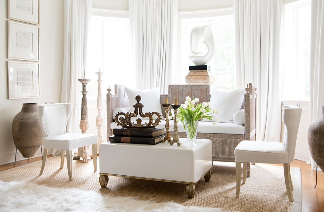"""Timeless French Decorating Ideas {Tara Shaw}. Walls painted Benjamin Moore's Linen White, and I loved how that looked with the white resin sculpture,"""" Tara says of the master bedroom's sitting area. Tara layered more white from there: drapes, a 22-ounce linen on the banquette, more Linen White in a high gloss on the coffee table."""