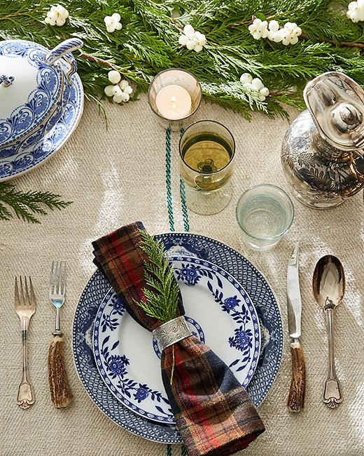 Mismatched blue-and-white plates, silver details, and an evergreen garland feel fresh on this autumnal holiday.