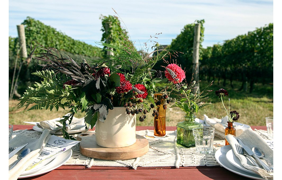 Big, lush gatherings of dahlias, blackberries, and greenery are set off by a sprinkling of small bud vases holding just a few stems.