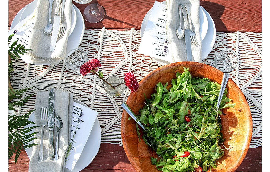 A macramé table runner and simple place settings create the perfect neutral but textured backdrop for the flowers and each family-style course. First up? Mixed greens from the vineyard's own greenhouse tossed in an earthy wood bowl.