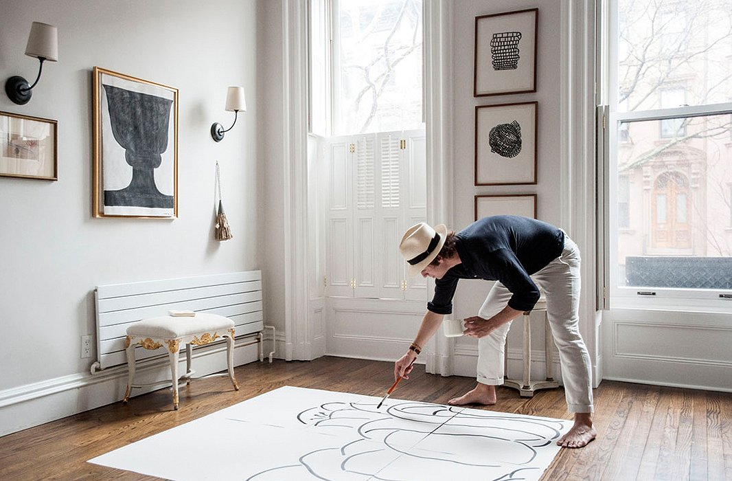 In his parlor, Pate displays his art alongside sconces from Visual Comfort and a Neoclassical bench bought on One Kings Lane.